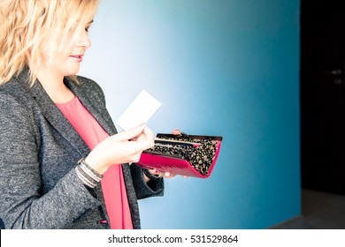 Pretty blond hair woman in pink red blouse and costume jacket with opened purse holding blank business card thinking - white to sky blue wall flat background