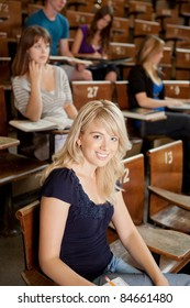 Pretty blond student in lecture theater looking at camera