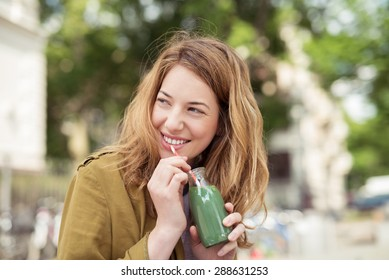 Pretty Blond Teen Girl Drinking a Bottle of Green Juice with Straw While Smiling Into Distance.