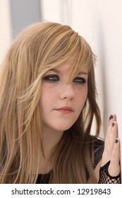 Pretty blond teen girl looks into the camera looking almost gothic