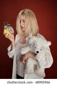 Pretty blond woman with bear and clock wakes up late