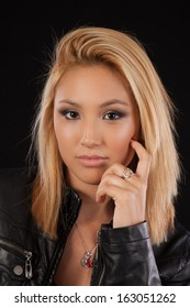 Pretty blond woman in black leather jacket, looking at the camera with a serious, thoughtful expression
