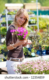 Pretty blond woman buying new plants for the garden