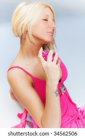 pretty blond woman holding bottle of perfume