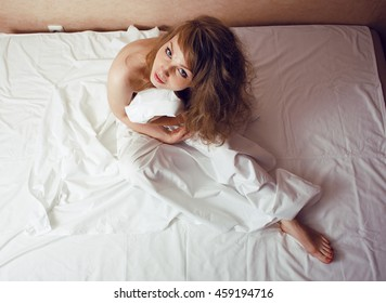 pretty blond woman laying in bed on white shits, sexy look romantic