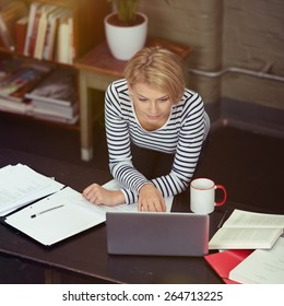 Pretty Blond Woman Leaning on the Table While Working on her Laptop with Documents, Books and Coffee Mug on the Sides.