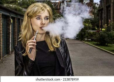Pretty blond woman smoking an e-cigarette standing in a street in a leather jacket exhaling a cloud a smoke from her mouth while looking off to the side