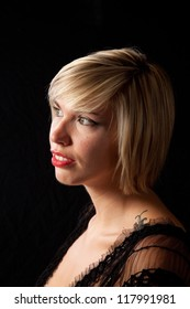 Pretty blond woman standing with  wearing a little black dress, looking left with a pensive, thoughtful expression and dramatic lighting