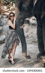 Pretty blond woman in stylish sunglasses and a dress with leopard print gently hugs elephant's trunk; friendship concept. Photo with noise. selective focus