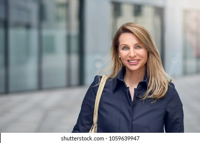 Pretty blond woman walking in an urban street looking at the camera with a lovely vivacious friendly smile in a head and shoulders portrait with copy space