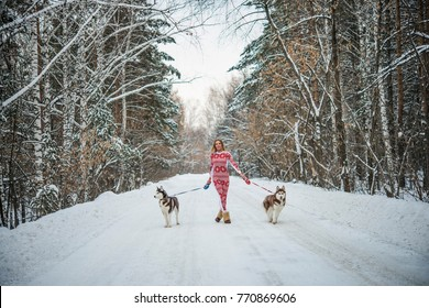 pretty blond woman walking in winter forest or park with couple of haski dog.