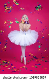 Pretty blonde ballerina in tutu skirt blowing colorful feathers on pink backdrop.