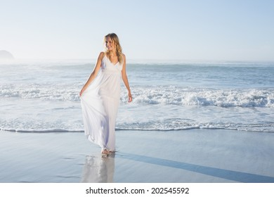 Pretty blonde at the beach in white sundress on a sunny day