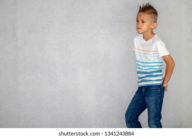Pretty blonde boy in t-shirt and jeans in, wall behind, copy space