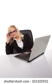 Pretty blonde businesswoman in glasses working on her laptop at her desk and pausing to look at the camera