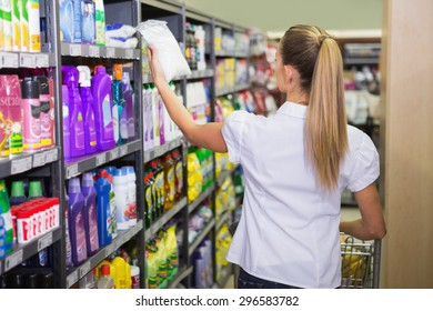 pretty blonde buy products with her trolley at supermarket