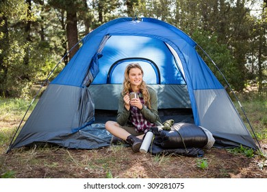 Pretty blonde camper smiling and sitting in tent in the nature