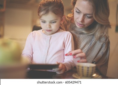 Pretty blonde Caucasian girl reading with her mother from tablet and smiling.