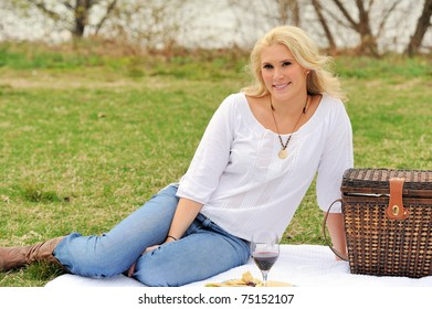 Pretty blonde female model relaxes on a white blanket with a glass of wine, plate of healthy food, and wicker like basket