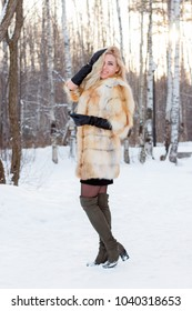 Pretty blonde in fur coat, leather gloves poses outdoor at winter day in forest