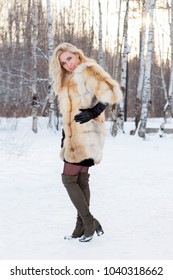 Pretty blonde in fur coat, leather gloves poses outdoor at winter day in park