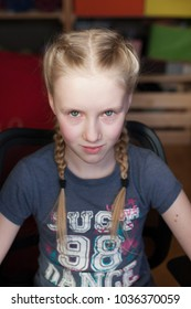 Pretty blonde girl with blue eyes and with two braids