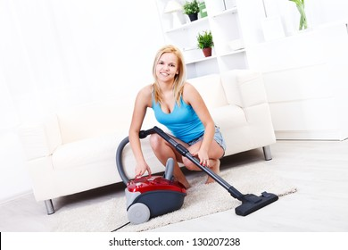 Pretty blonde girl cleans the living room with the vacuum cleaner