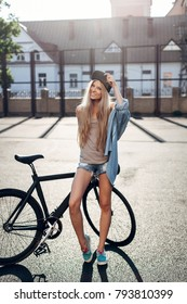 Pretty blonde girl in denim outfit posing in summer with sport bicycle