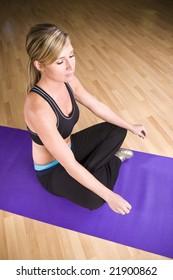 Pretty blonde girl doing yoga on a mat