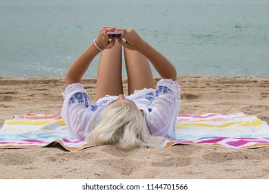 pretty blonde girl with the phone on the beach
