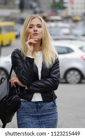 Pretty blonde girl posing in the street, cars, autos at background blurred. The girl is dressed in a black leather jacket, a white sweater and a denim skirt. Black bag.