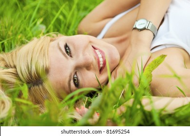 Pretty blonde  girl relaxing outdoor in green grass