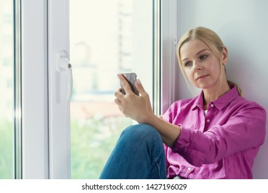 Pretty blonde girl sitting on a window and smartphone in hands