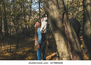 Pretty blonde girl standing by her grey horse in the countryside