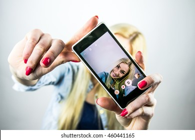 Pretty blonde girl take selfies with smartphone. Female person take a pictures of herself. Taking a picture with phone