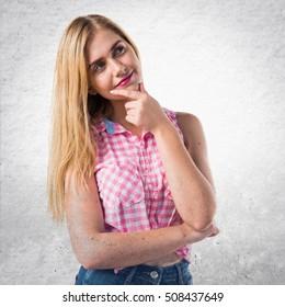 Pretty blonde girl thinking on textured background