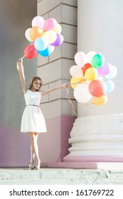 pretty blonde girl in white dress holds two bunches of multicolored balloons in front of old building with columns
