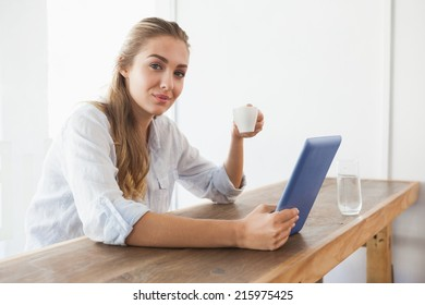 Pretty blonde having coffee while using tablet at the coffee shop
