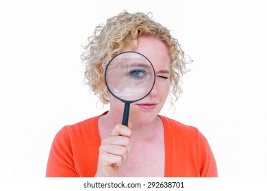 Pretty blonde looking at magnifying glass on white background