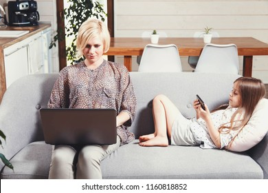 Pretty blonde mother working with laptop and cute little brunette girl laying on the sofa and playing games on the smartphone