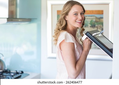 Pretty blonde opening the oven at home in the kitchen