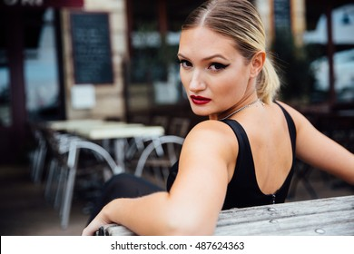 Pretty blonde rests on a bench and turns her head.