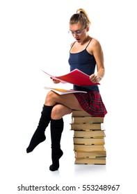 Pretty blonde school girl sitting on many books and holding college notes and making surprise gesture