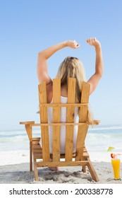 Pretty blonde sitting in deck chair with a cocktail on a sunny day