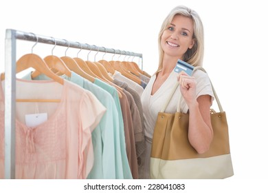 Pretty blonde smiling at camera by clothes rail on white background