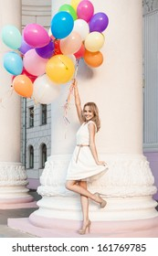 pretty blonde smiling girl in white summer dress holds a bunch of multicolored balloons in front of old column