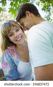 Pretty blonde smiling while hugging boyfriend in the park on a sunny day