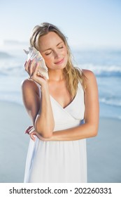 Pretty blonde standing at the beach in white sundress listening to conch on a sunny day