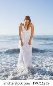 Pretty blonde standing in the sea at the beach in white sundress on a sunny day