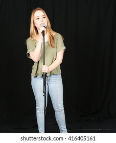 pretty blonde teen girl singing into microphone
